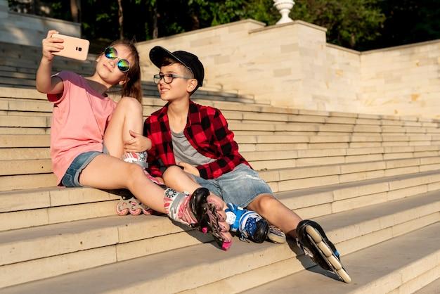 Garçon et fille prenant un selfie Photo gratuit