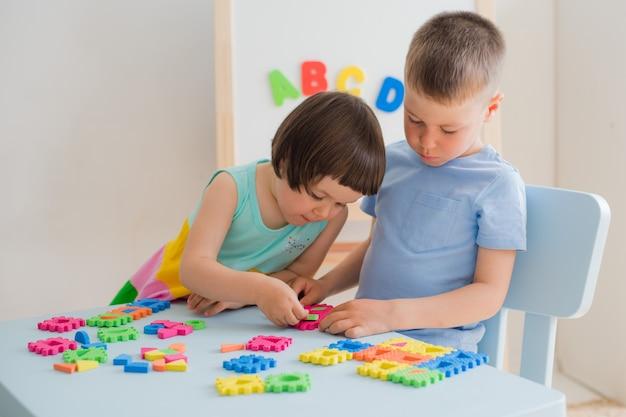Un garçon et une fille rassemblent un puzzle léger à la table Photo Premium