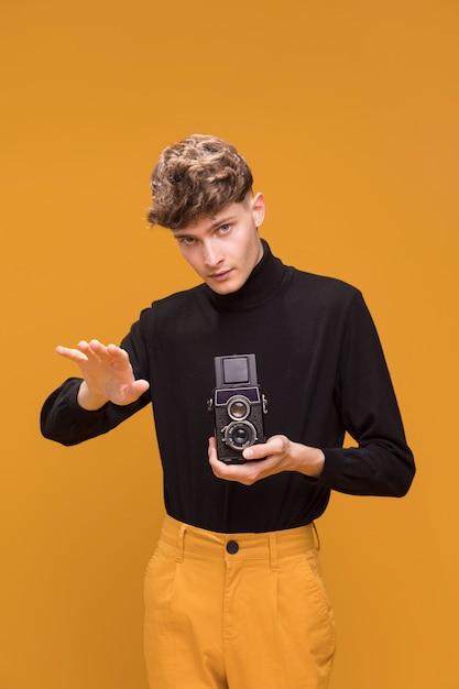 Garçon filme avec un caméscope dans une scène jaune Photo gratuit