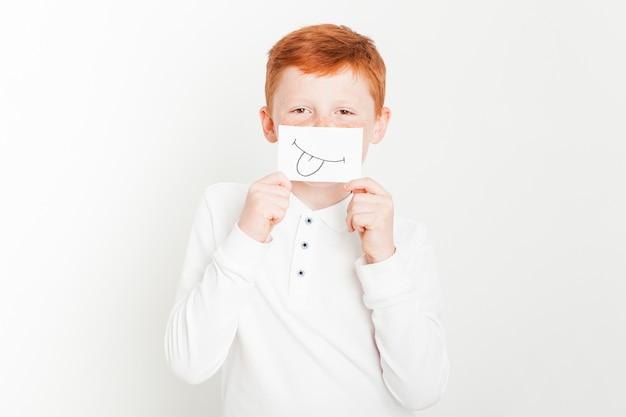 Garçon de gingembre tenant la carte devant le visage Photo gratuit