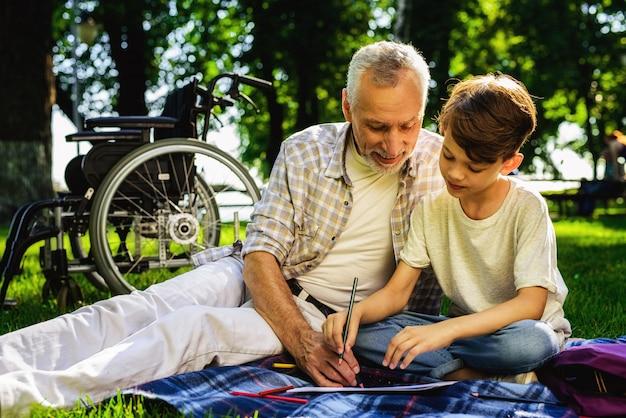 Garçon et grand-père dessinent un pique-nique familial Photo Premium
