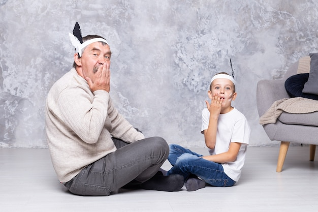 Garçon Et Grand-père Jouent Des Indiens Sur Un Mur Gris. Senior Homme Et Petit-fils Jouent Injun Dans Le Salon. Famille Ensemble Photo Premium