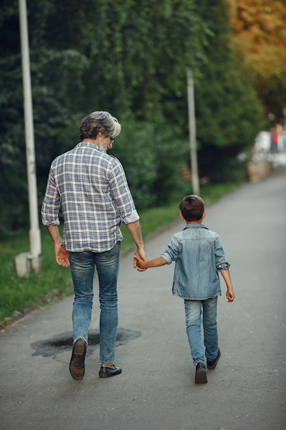 Garçon Et Grand-père Marchent Dans Le Parc. Vieil Homme Jouant Avec Son Petit-fils. Photo gratuit