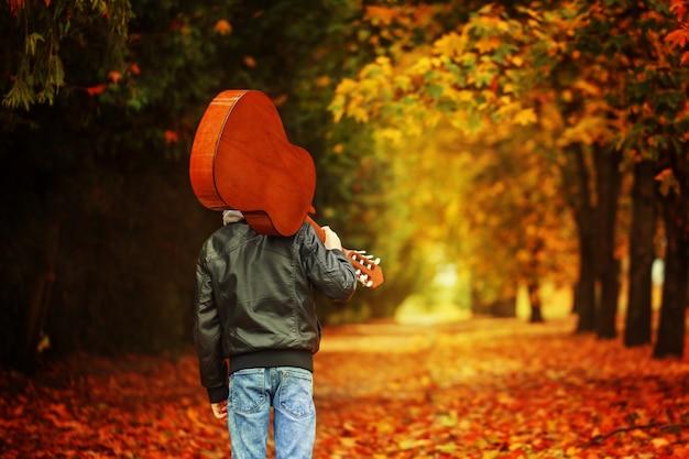 Garçon avec guitare, marchant sur la route d'automne. vue arrière Photo Premium