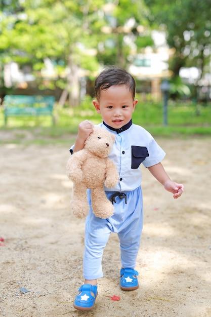 Garçon heureux bambin marcher dehors avec holding ours en peluche dans le parc. Photo Premium