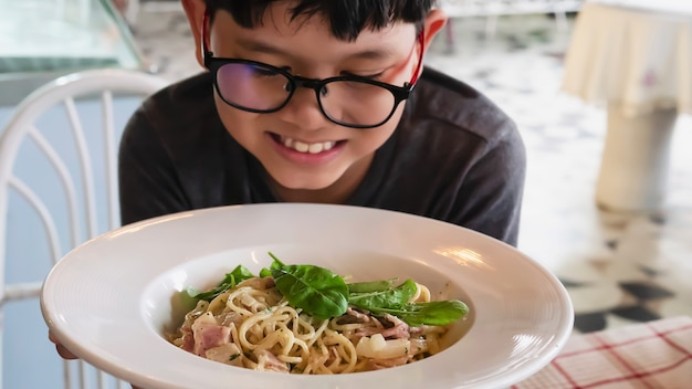Garçon heureux manger spaghetti carbonara recette Photo gratuit