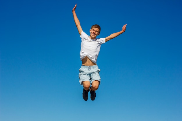 Garçon heureux, sautant dans le ciel bleu Photo Premium