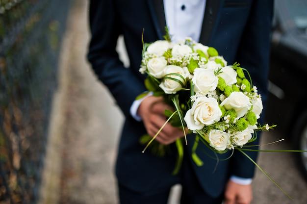 Garçon d'honneur tenir en main deux bouquets pour demoiselles d'honneur Photo Premium