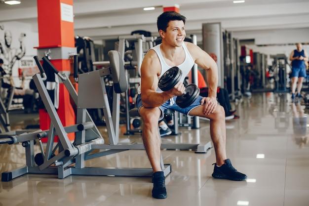 Un garçon jeune et athlétique est engagé dans les sports dans la salle de gym Photo gratuit