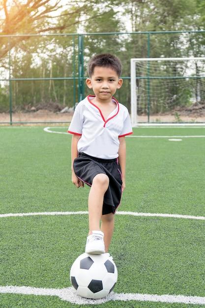 Le garçon jouait au football sur le terrain de football avec bonheur. Photo Premium