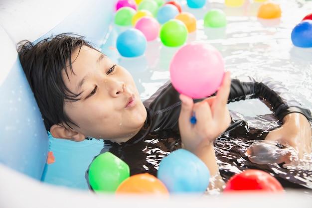 Garçon jouant avec une balle colorée dans un petit jouet de piscine Photo gratuit