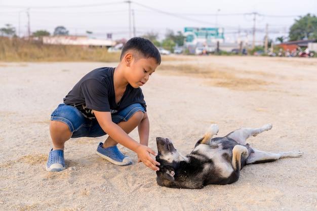 Garçon jouant avec des chiens noirs sur le sol Photo Premium