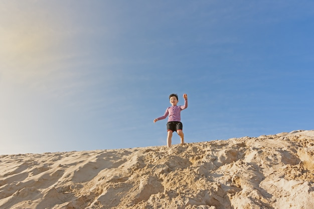 Garçon jouant dans les dunes Photo Premium