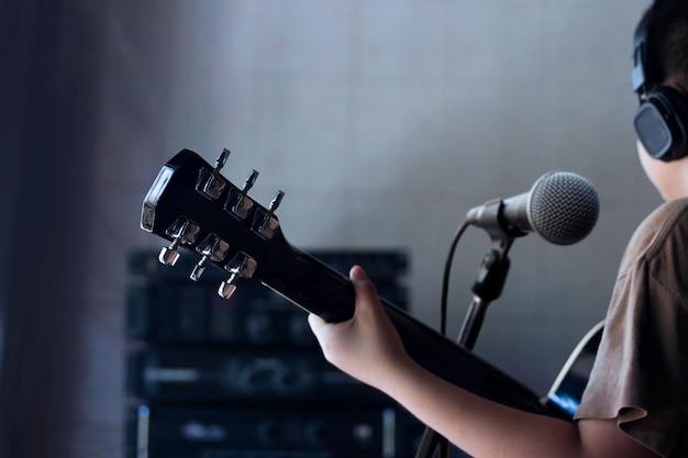 Garçon Jouant De La Guitare Dans Le Fond De La Salle D'enregistrement Photo Premium