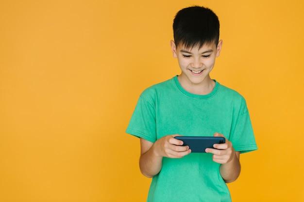 Garçon jouant à un jeu au téléphone Photo gratuit