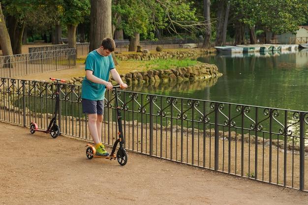 Garçon Jouant Avec Son Scooter Dans Le Parc Photo Premium