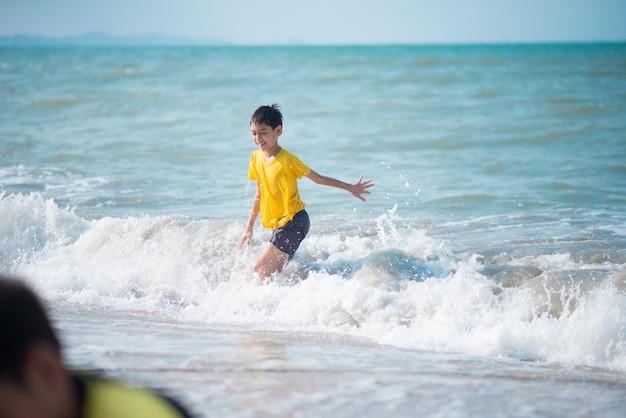 Garçon jouant des vagues et du sable sur la plage Photo Premium