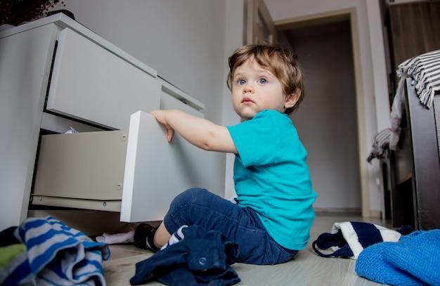 Garçon joue avec des vêtements de placard Photo Premium