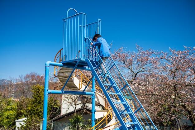 Garçon jouer curseur dans le parc du printemps, matsumoto Photo Premium