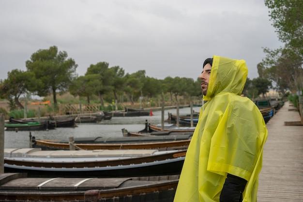 Garçon Un Jour De Tempête Avec Un Imperméable. Photo Prise Au Port De Catarroja à Valence, Espagne. Photo Premium