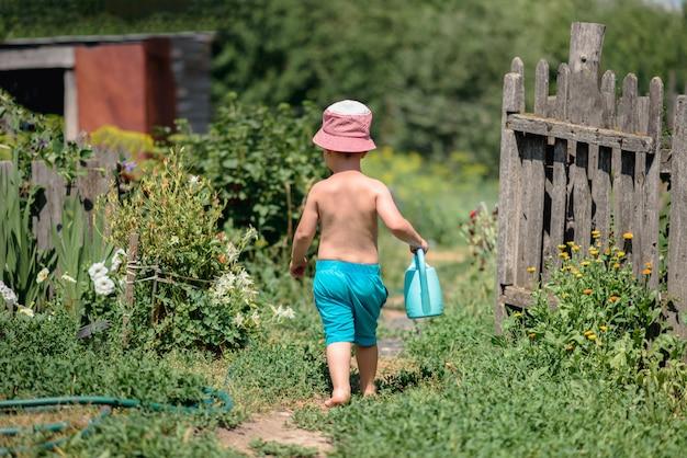 Un garçon joyeux avec un arrosoir traverse le jardin pieds nus pour arroser les fleurs. Photo Premium