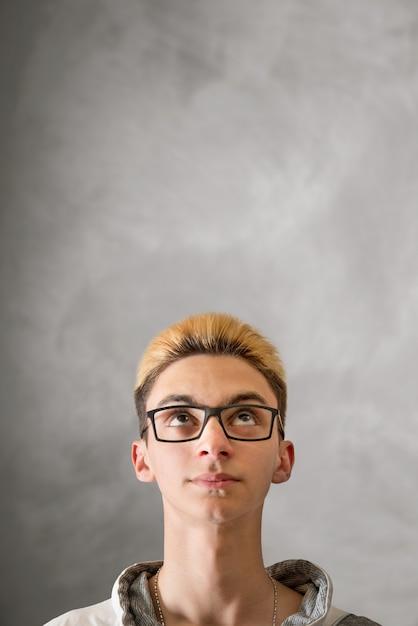 Garçon levant les yeux sur fond gris Photo Premium