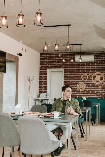 Garçon mangeant dans un restaurant Photo gratuit