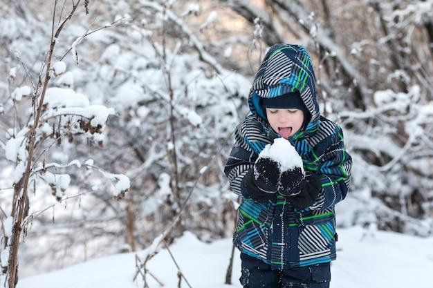 Garçon mangeant de la neige en hiver. Photo Premium