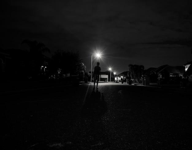 Garçon Marchant Seul La Nuit Sous Les Feux De Rue Photo gratuit