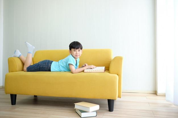Garçon mignon asiatique, lecture de manuel et de literie sur le canapé. Photo Premium