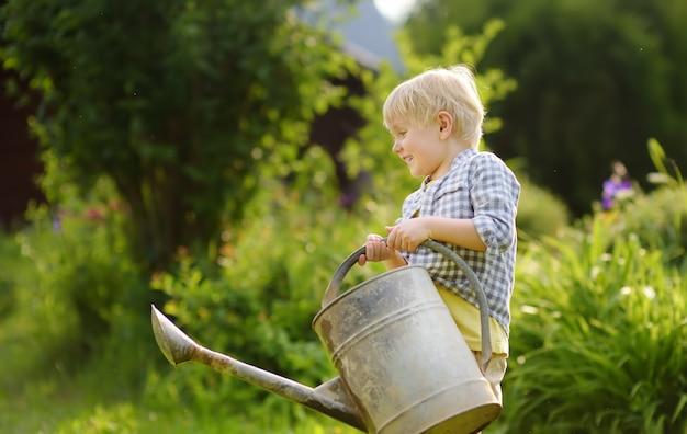 Garçon mignon bambin, arrosage des plantes dans le jardin à la journée ensoleillée d'été. Photo Premium