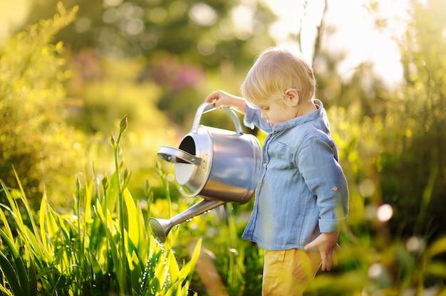 Garçon mignon bambin, arrosage des plantes dans le jardin à la journée ensoleillée d'été Photo Premium