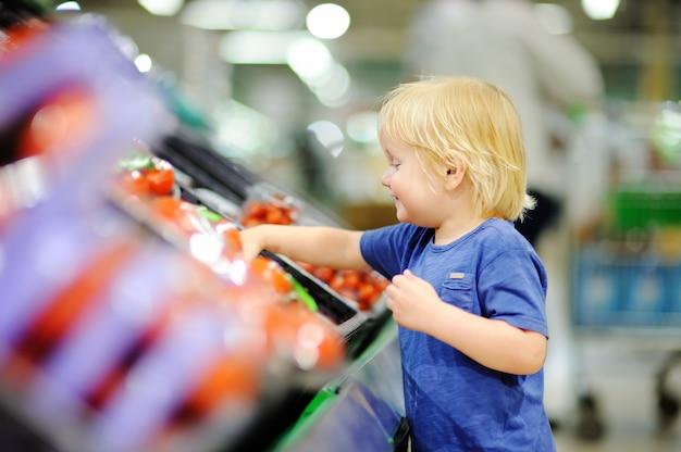 Garçon mignon bambin dans un magasin d'alimentation ou un supermarché en choisissant des tomates fraîches. mode de vie sain pour jeune famille avec enfants Photo Premium
