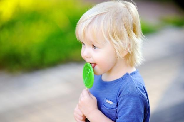 Garçon mignon bambin avec grosse sucette verte. enfant mangeant des friandises sucrées. bonbons pour les jeunes enfants. plaisirs d'été en plein air Photo Premium