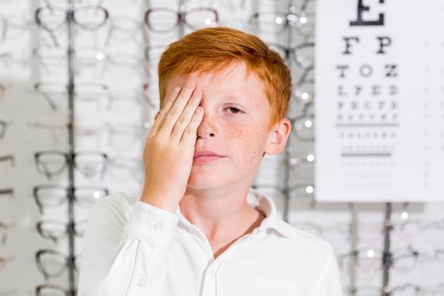 Un garçon mignon a couvert son œil avec la main, debout dans une clinique d'optique Photo gratuit