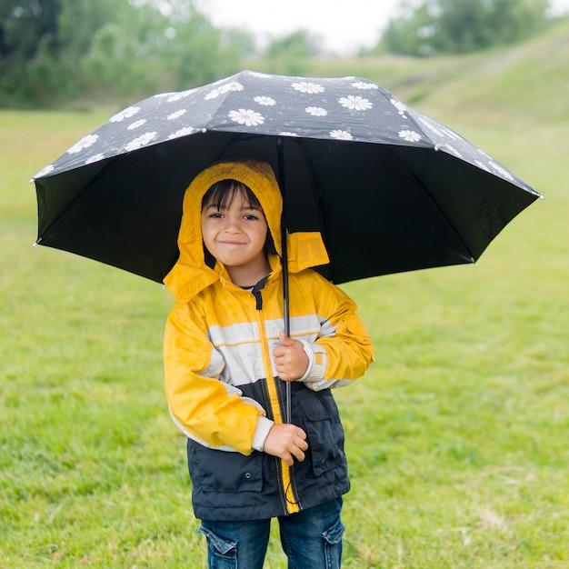 Garçon Mignon En Imperméable Et Parapluie Photo gratuit