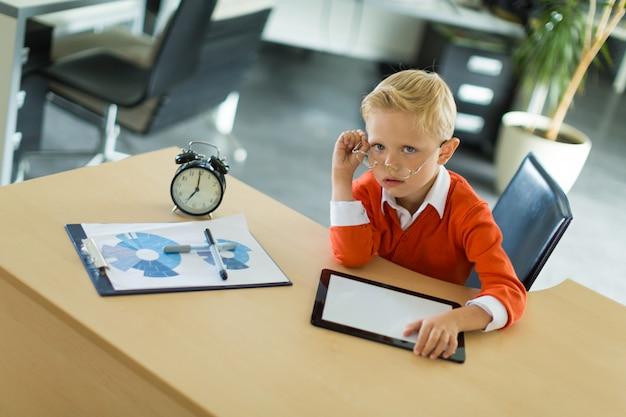 Un garçon mignon s'asseoir au bureau au bureau et utilise une tablette pc Photo Premium
