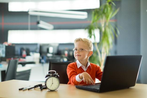 Un garçon mignon s'asseoir au bureau du bureau et utilise un ordinateur Photo Premium