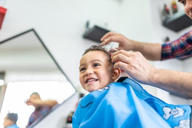 Garçon Mignon Se Faire Couper Les Cheveux Dans Un Salon De Coiffure. Concept De Beauté. Photo Premium