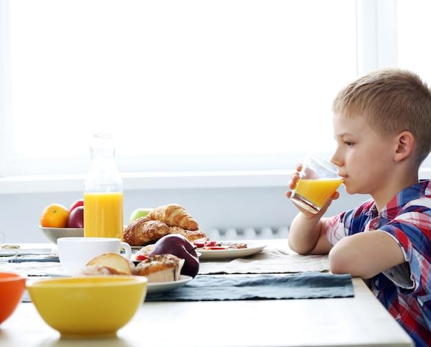 Garçon mignon avec un verre de jus Photo gratuit