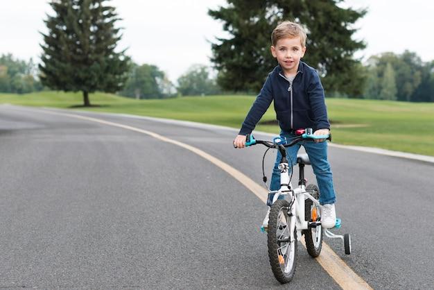 Garçon Monté Sur Sa Vue De Face De Vélo Photo gratuit