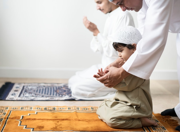 Un garçon musulman apprend à faire dua à allah Photo Premium