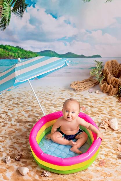 Garçon Nageant Dans Une Piscine Gonflable Sous Un Parasol Sur Une Plage De Sable Avec Des Palmiers Au Bord De La Mer Photo Premium