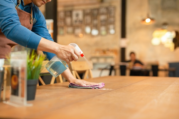 Garçon de nettoyage de la table avec un spray désinfectant sur la table du restaurant. Photo Premium