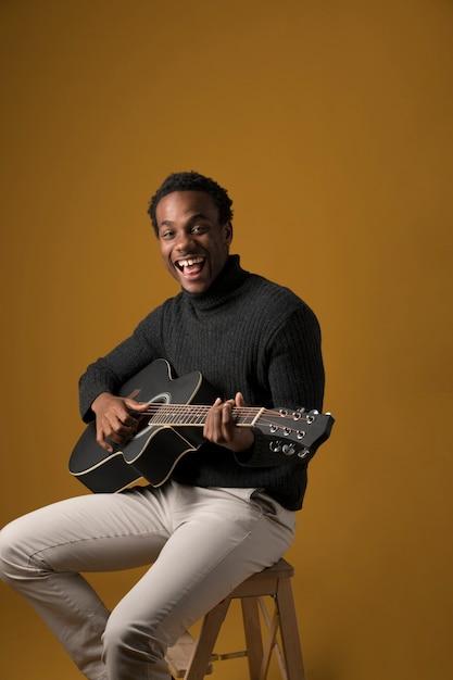 Garçon noir jouant de la guitare Photo gratuit