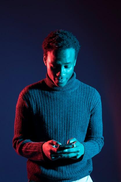Garçon noir posant avec une lumière bleue Photo gratuit