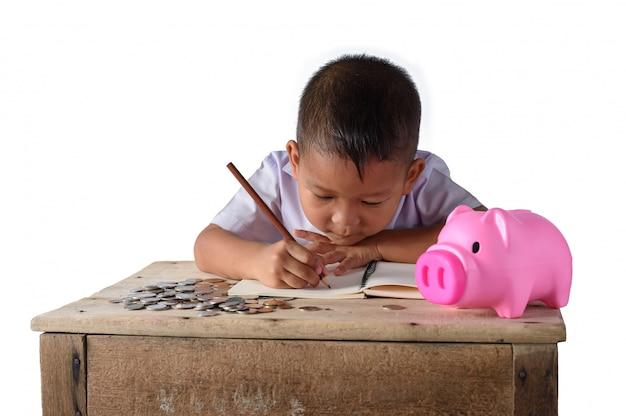 Garçon de pays asiatique mignon notez les recettes et les pièces de monnaie avec la tirelire Photo Premium