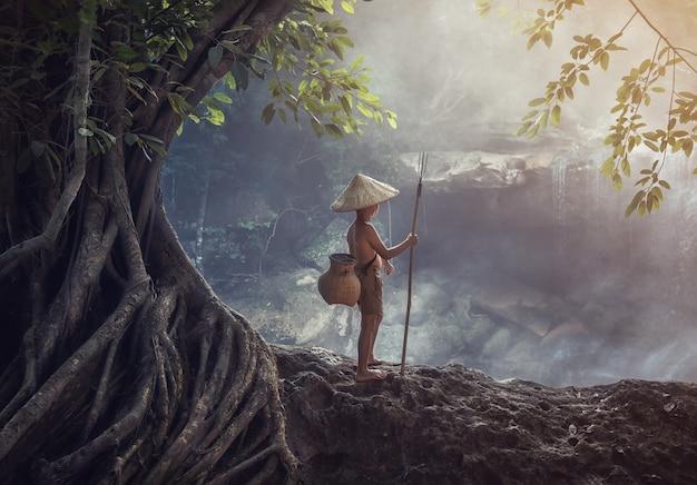 Garçon pêchant dans la crique, campagne de thaïlande Photo Premium