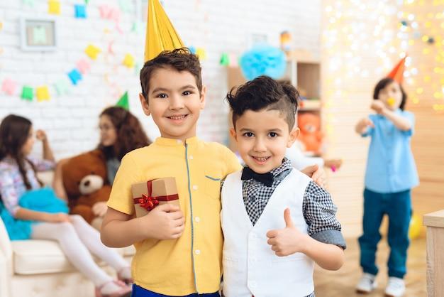 Garçon et petit invité avec un cadeau à la fête d'anniversaire Photo Premium