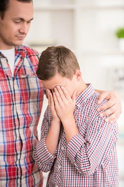 Un garçon pleure tandis que son père le gronde. Photo Premium